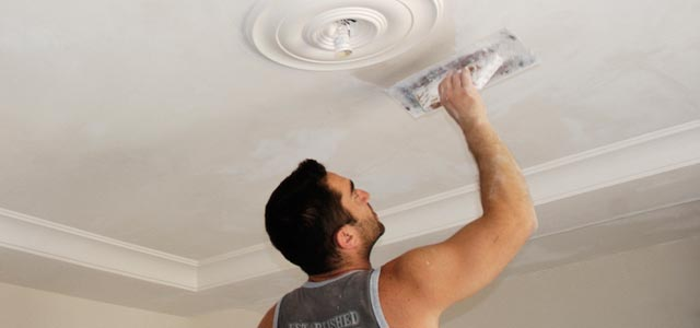 a man plastering the ceiling